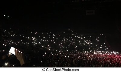 Unrecognizable fans holding flashlights in theirs hands in face of the stage. Atmosphere of the concert. Cheering crowd