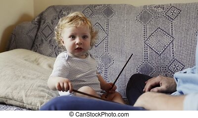 Unrecognizable father at home with his little son sitting on...