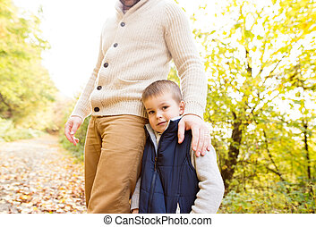Unrecognizable father with his son in autumn forest.
