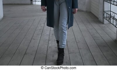 Closeup of woman's shoes, person walking, elegant young girl . unrecognizable female in black boots stepping forward outdoors. Person moving along veranda with wooden floor. Close up on thin legs