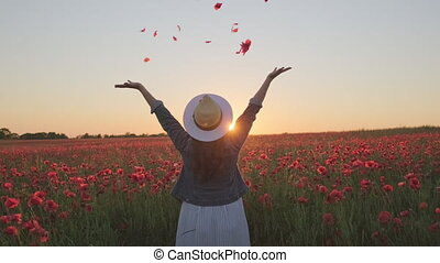 Pan right view of anonymous woman in hat and denim jacket throwing poppy petals in air while having fun in blooming field during sunset