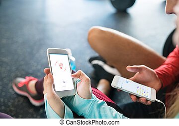 Unrecognizable fit couple in gym with smartphones. - ...