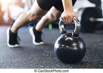 Unrecognizable fit man in gym doing push ups on kettlebells...