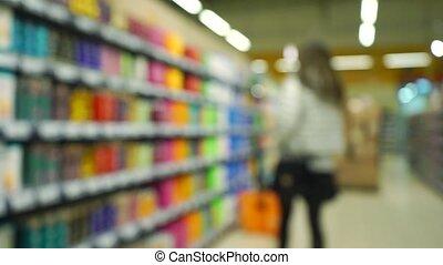 Unrecognizable girl chooses shampoo in supermarket. Bokeh slow motion video