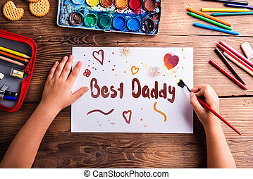 Fathers day composition. Hands of unrecognizable child painting picture for her father. Studio shot on wooden background.