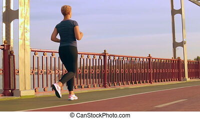 unrecognizable girl training cardio outdoors - back view...