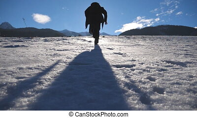 Unrecognizable guy jogging on snowy field at sunny winter day. Young man running on snowy meadow. Sun light and blue sky at background. Concept of holiday or vacation. Rear back view Slow motion