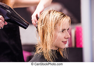 Unrecognizable hairdresser drying hair of her beautiful ...