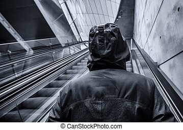 Unrecognizable hooded person on moving escalator