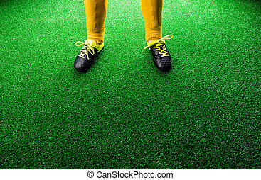 Unrecognizable little football player against green grass