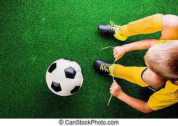 Unrecognizable little football player against green grass, studi