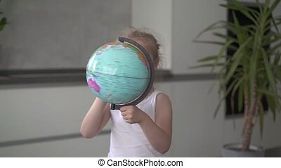 Unrecognizable little girl whirling a globe at home slow motion