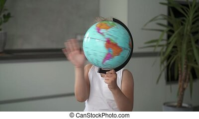 Unrecognizable little girl whirling a globe at home