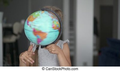 Unrecognizable little girl whirling a globe in her room