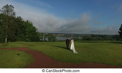 Unrecognizable lovely wedding couple walking on the grass