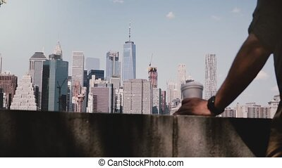 Unrecognizable male hand taking a coffee cup at incredible river bank skyline panorama of sunny Manhattan, New York City