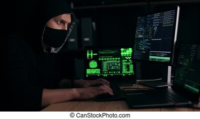 Anxious male in mask and hood typing on computers feeling lack of time, cybercrime