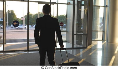 Unrecognizable man going through glass automatic door of modern airport with his luggage to city street. Businessman walking to cars parking from terminal and pulling suitcase on wheels. Slow motion