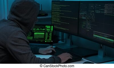 Unrecognizable man hacker wearing sweatshirt with hood typing on computer keyboard and breaking password. Side view of dangerous hooded computer hacker infecting system with cyber virus.