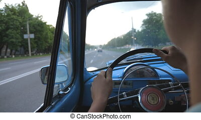 Unrecognizable man holding hands on steering wheel and driving his old retro car on asphalt road. Young guy riding a blue vintage automobile on the city street. Close up Slow motion Rear back view