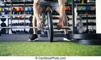 Unrecognizable man in gym changing weigts on heavy barbell.