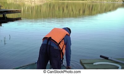 Unrecognizable man in lifejacket in a boat at the evening