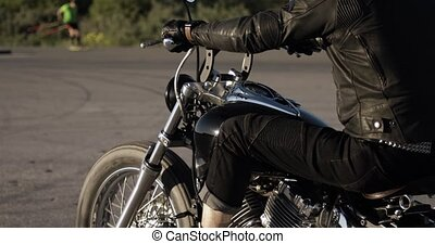 Unrecognizable man is riding a motorcycle on the road, average plan video.
