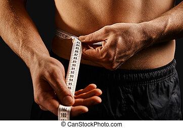 Unrecognizable sportsman measuring waist with centimeter tape