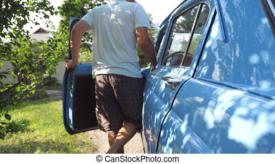 Unrecognizable man opening door and get into his old retro car at countryside. Young guy in hat going to drive on his blue vintage automobile on sunny summer day. Rear back view Close up Slow Motion