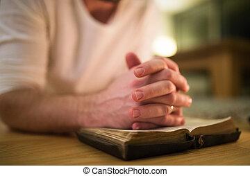Unrecognizable man praying, kneeling on the floor, hands on...