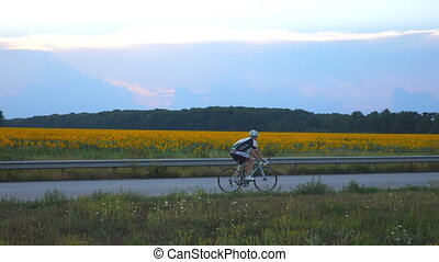 Unrecognizable man riding bicycle in country road. Sporty...