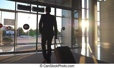 unrecognizable, man te lopen, door glas, automatische deur, van, moderne, luchthaven, om te, stad straat, en, het trekken, koffer, op, wheels., zakenman, gaan, van, terminal, om te, auto's, parkeren, met, zijn, luggage., achterk bezichtiging