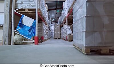 workers move along the shelves with products warehouse indoors