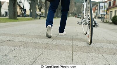 Unrecognizable man with bicycle in town. - Unrecognizable...