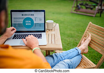 Unrecognizable man with laptop working outdoors in garden, home office concept.