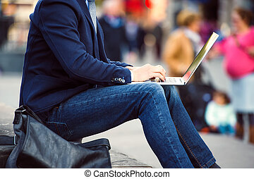 Unrecognizable manager sitting on stairs on crowded Piccadilly Circus, London, working on laptop