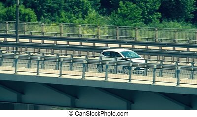 Unrecognizable modern compact car moving along the bridge -...