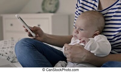 Unrecognizable mother with baby son, sitting on bed, smartphone