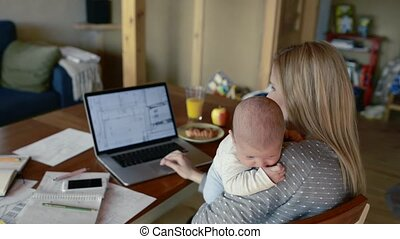 Unrecognizable mother with son in the arms, working on laptop