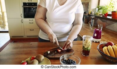 Unrecognizable overweight woman preparing healthy smoothie...