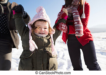 Unrecognizable parents with their daughter on a walk in winter