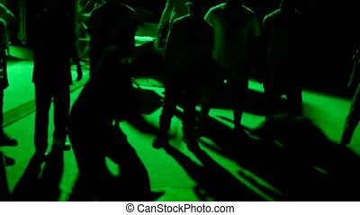 Unrecognizable people dancing outdoors green light