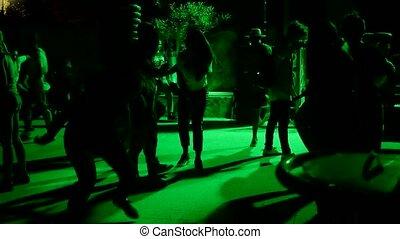Unrecognizable people dancing outdoors under green light