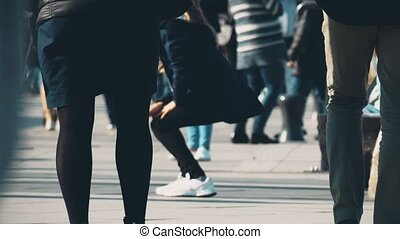 Unrecognizable people walk along pedestrian city street