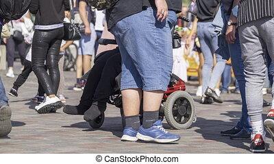 Unrecognizable people walking along street in summer