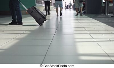 Unrecognizable people with baggages walking in terminal airport. slow motion. Close up. 840x2160