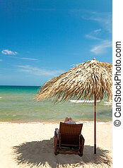Unrecognizable person reading book in canvas chair on beautiful tropical beach