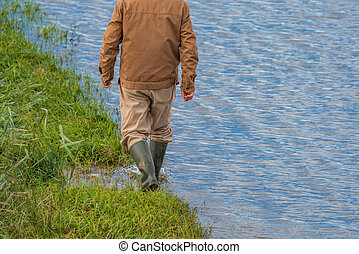 Unrecognizable person walking near flooded road, rear view
