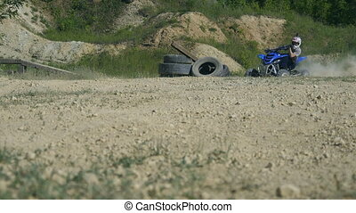 Unrecognizable racer in helmet on ATV enters the turn at...