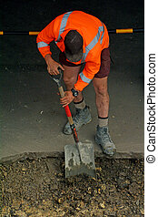 Road worker digging with shovel